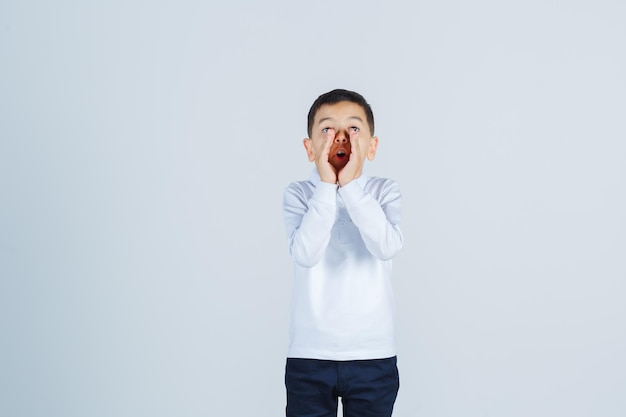 Garotinho gritando ou anunciando algo em camisa branca, calça e parecendo animado. vista frontal.