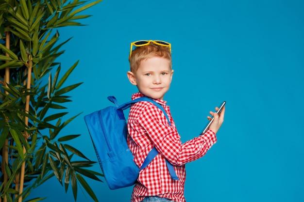 Garotinho hipster com mochila e óculos de sol, segurando o telefone