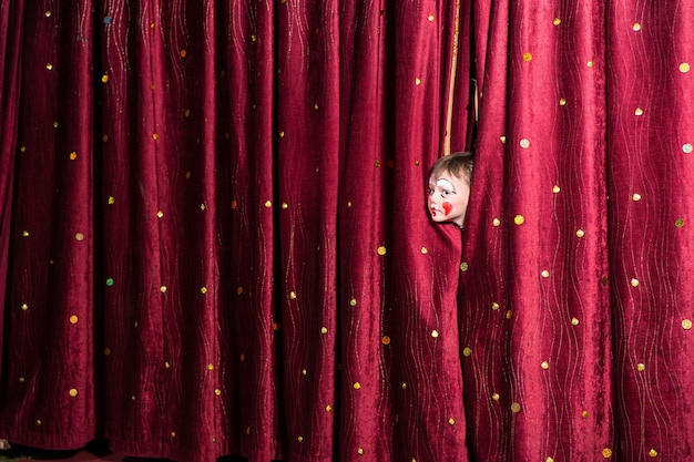 Garotinho impaciente no palco enfiando a cabeça para fora por entre as cortinas fechadas enquanto olha para ver qual é o atraso para o início da peça ou pantomima