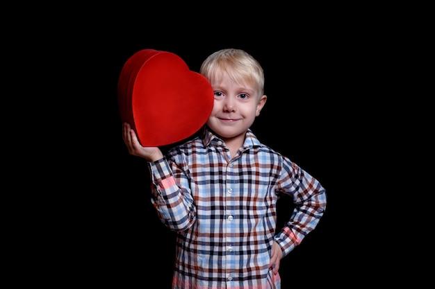 Garotinho, inclina-se contra sua bochecha caixa de forma de coração vermelho no preto