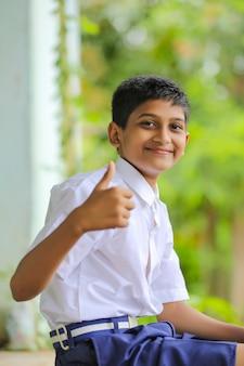 Garotinho indiano fofo em uniforme escolar mostrando golpes
