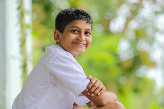 Garotinho indiano fofo em uniforme escolar