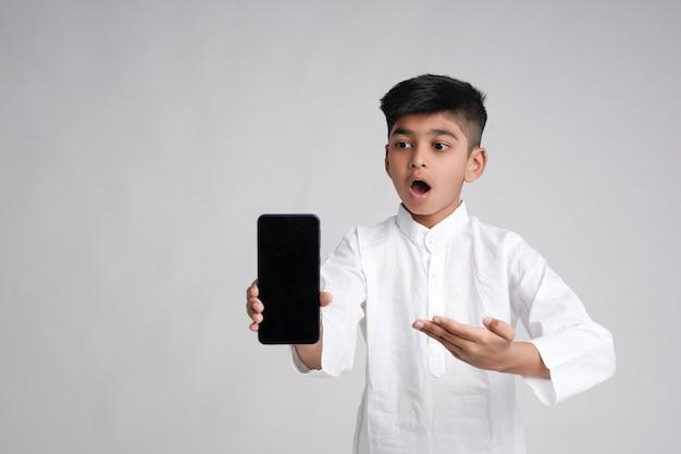 Garotinho indiano fofo mostrando a tela do smartphone com espaço de cópia sobre fundo branco