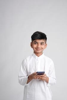 Garotinho indiano fofo usando telefone inteligente