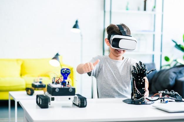 Garotinho inteligente e entusiasmado sentado à mesa enquanto faz experiências com uma mão robótica humanóide e óculos de realidade virtual