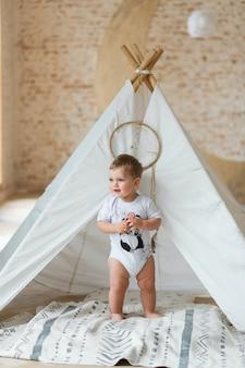 Garotinho jogando em uma tenda no interior do apartamento com parede de tijolos.