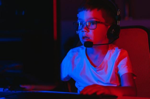 Garotinho jogando videogame no quarto escuro