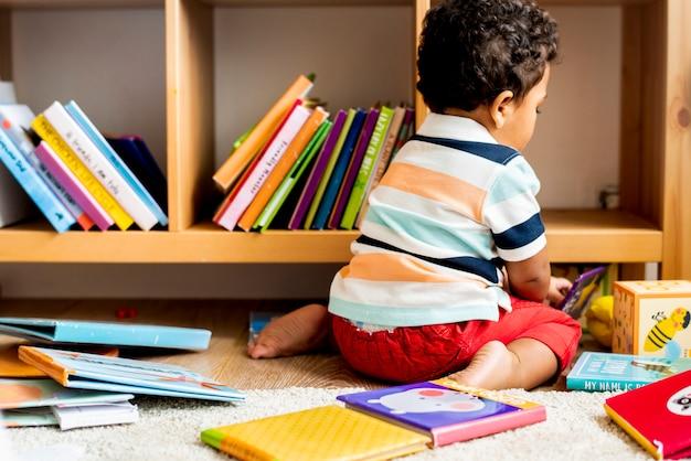 Garotinho, lendo um livro na biblioteca