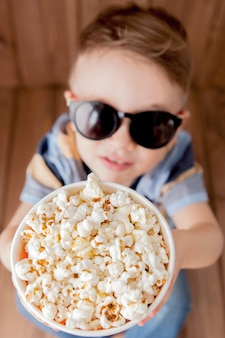 Garotinho lindo menino 2-3 anos de idade, óculos de cinema 3d imax segurando balde para pipoca, comendo fast-food em fundo de madeira.