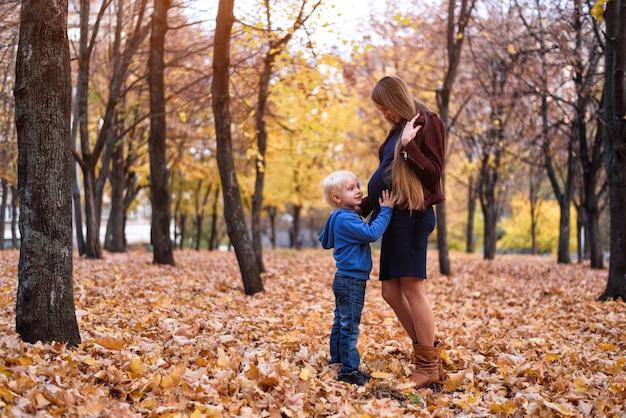 Garotinho loiro abraça a barriga da mãe grávida. parque de outono ao fundo