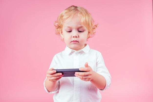 Garotinho loiro cachos penteado em um terno de negócio assistindo algo interessante telefone celular. criança bonito na moda em um fundo rosa no estúdio.