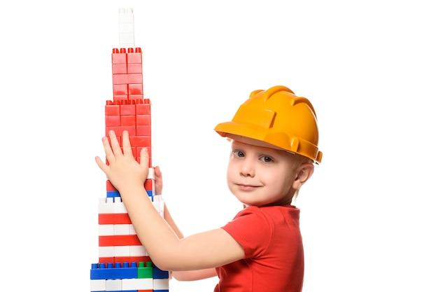 Garotinho loiro com o capacete de construção e uma camisa vermelha em pé perto da torre construída a partir de designer de peças. retrato. isole em fundo branco.