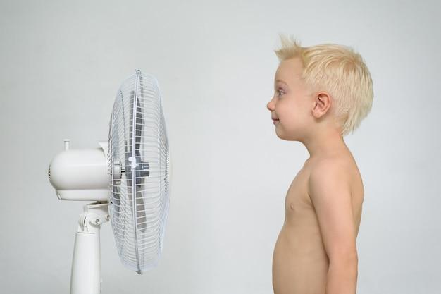 Garotinho loiro com torso nu está perto de um ventilador. conceito de verão