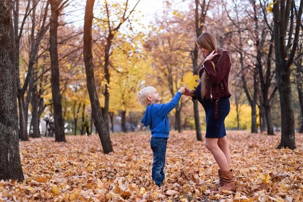 Garotinho loiro dá folha amarela à mãe grávida. parque de outono ao fundo