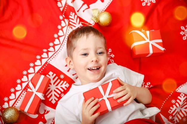 Garotinho loiro deitado no chão, criança fofa segurando um presente de natal