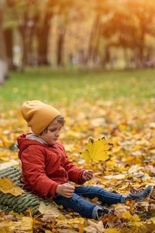 Garotinho loiro e fofo se divertindo ao ar livre no parque no outono, na folhagem sob uma árvore, com uma jaqueta vermelha quente de outono e um chapéu amarelo fofo