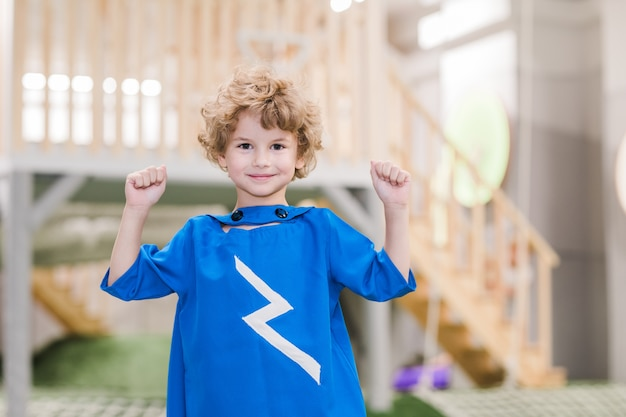 Garotinho loiro sorridente com fantasia azul de super-homem olhando para você enquanto brinca no centro infantil