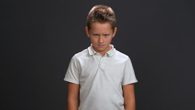 Garotinho malvado olhando para a frente usando camisa pólo branca e calça preta isolada na parede preta