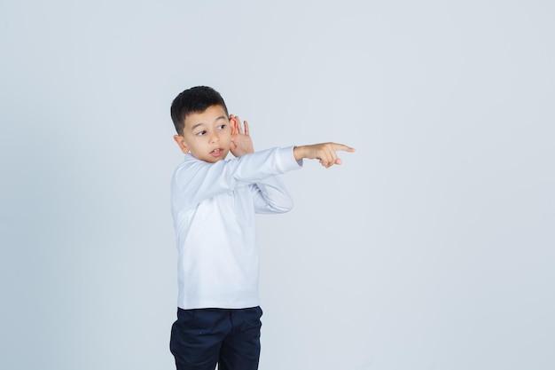 Garotinho mantendo a mão atrás da orelha, apontando para longe em camisa branca, calça e parecendo curioso. vista frontal.