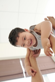 Garotinho mestiço alegre nas mãos de seu pai carinhoso levantando sua cabeça