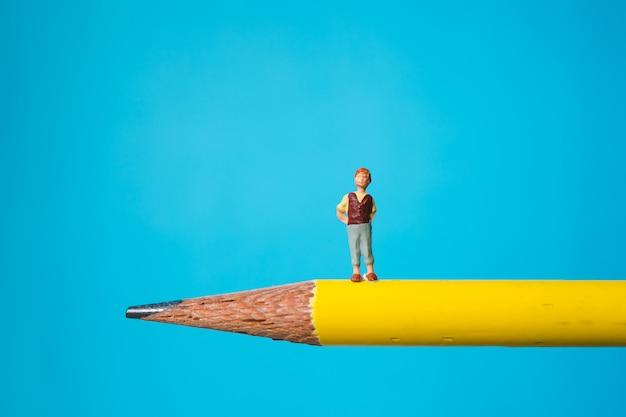 Garotinho miniatura em pé no lápis amarelo usando como conceito de família e educação
