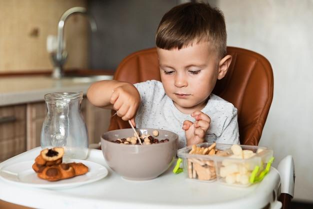 Garotinho, misturando cereais em uma tigela
