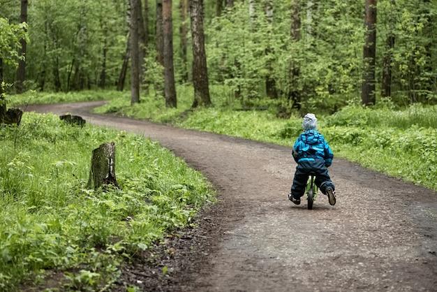 Garotinho, montando runbike na estrada da floresta