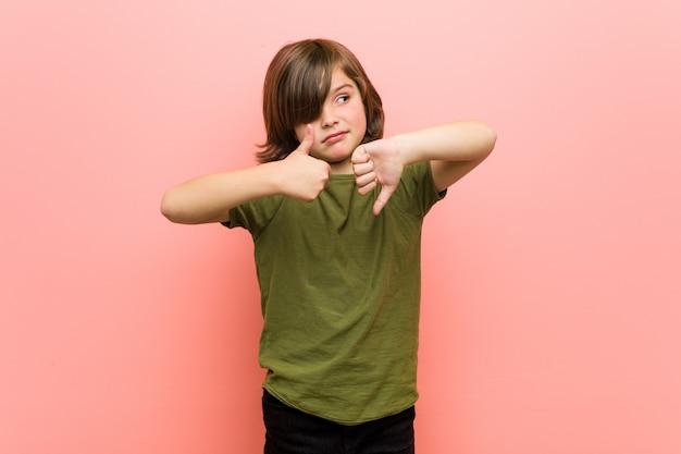 Garotinho, mostrando os polegares para cima e os polegares para baixo, difícil escolher o conceito