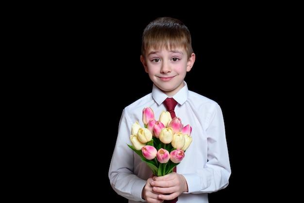 Garotinho na camisa branca dá um buquê de tulipas.