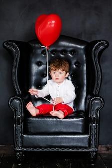 Garotinho na camisa branca e calça vermelha, sentado na poltrona com balão de coração vermelho no dia dos namorados