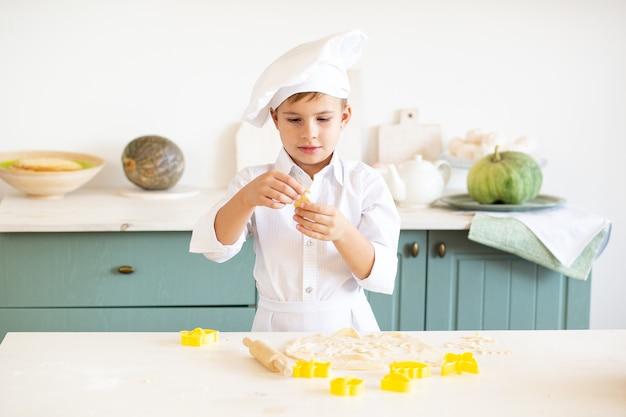 Garotinho na fantasia de cozinheiro assando biscoitos