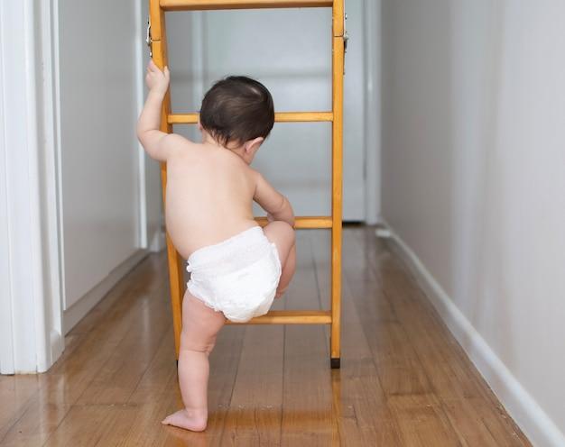Garotinho na fralda está tentando subir a escada interna de madeira