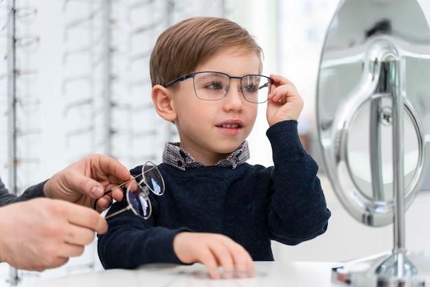 Garotinho na loja experimentando óculos
