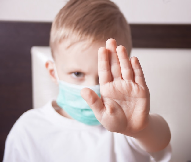 Garotinho na máscara facial mostrando sinal de stop com a mão