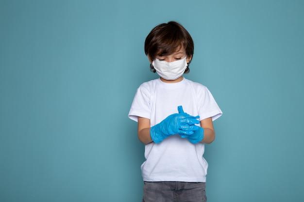 Garotinho na máscara protetora estéril branca e luvas azuis na parede azul