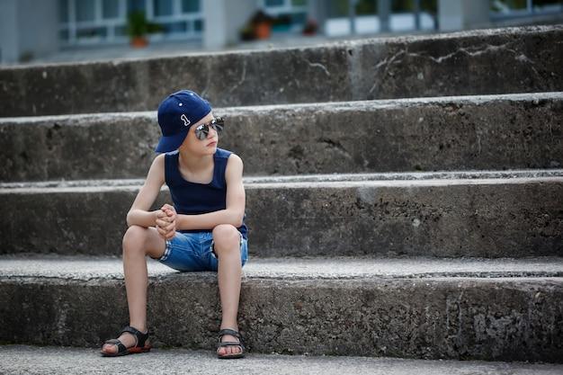 Garotinho na moda de óculos escuros e boné. infância. horário de verão