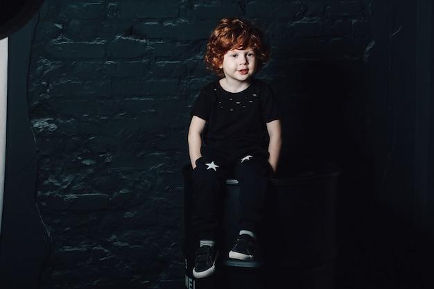 Garotinho na moda em roupas escuras, posando no quarto mal iluminado