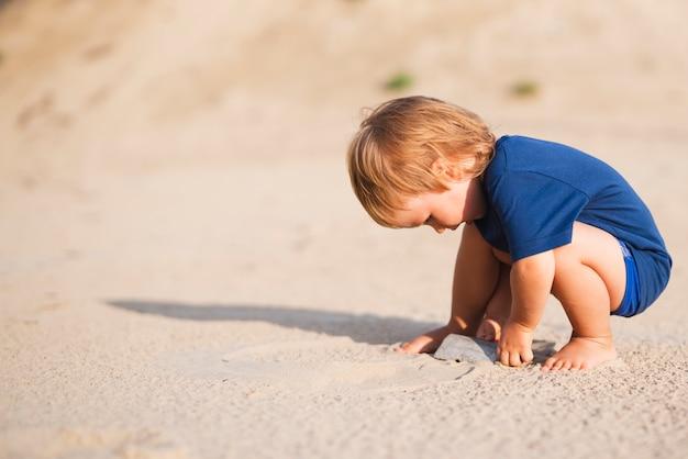 Garotinho na praia brincando com areia