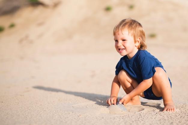 Garotinho na praia, olhando para longe