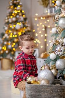 Garotinho não quer decorar a árvore de natal. feliz natal e feliz ano novo