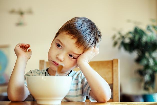 Garotinho não quer tomar seu café da manhã, falta de apetite das crianças