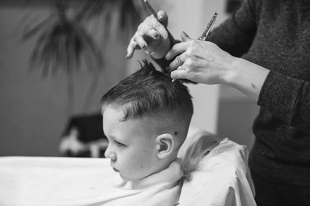 Garotinho no cabeleireiro. a criança tem medo de cortar o cabelo. mãos de cabeleireiro fazendo penteado para menino, close-up. corte de cabelo elegante para meninos.