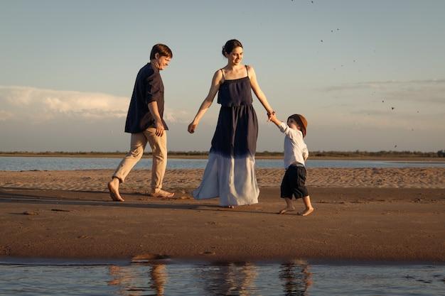 Garotinho no panamá marrom, caminhando na praia com seus pais.