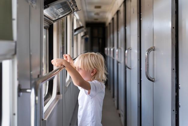 Garotinho no vagão de trem. criança loira olhando pela janela do trem.