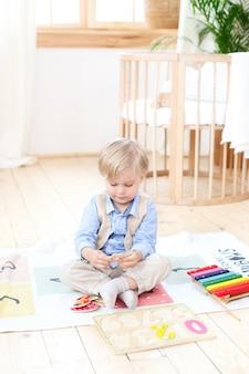 Garotinho. o menino brinca com brinquedos de madeira em casa. brinquedos educativos de madeira para a criança. retrato de um menino sentado no chão na sala de crianças no escandinavo. brinquedos ecológicos, decoração de quarto de crianças