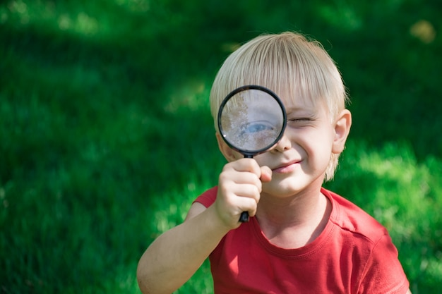 Garotinho olhando através de lupa. filho curioso. criança brinca com lupa