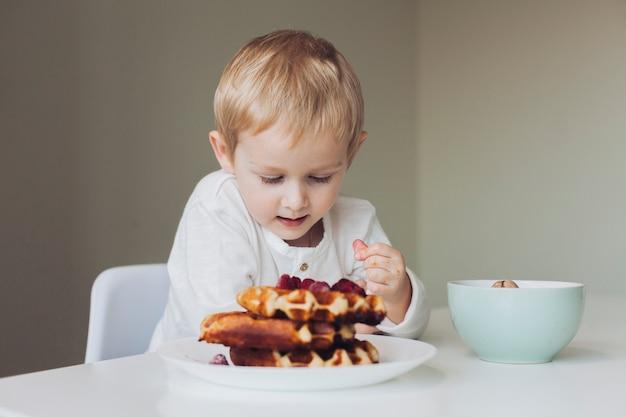 Garotinho olhando waffle