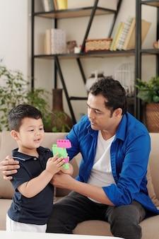 Garotinho orgulhoso mostrando para o pai uma figura que fez de tijolos de brinquedo coloridos quando eles vão passar o fim de semana juntos em casa