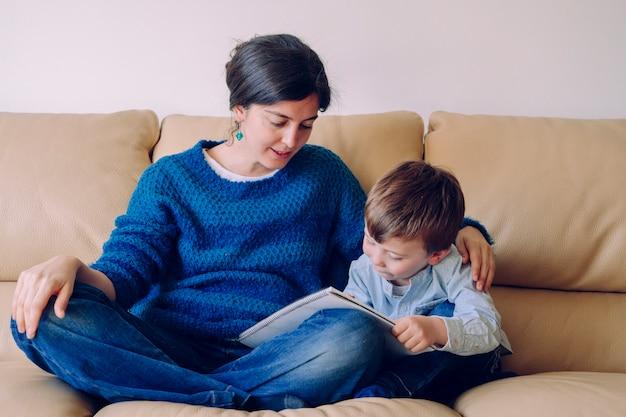 Garotinho, ouvindo uma história de um livro com a mãe. estilo de vida com crianças em casa. garotinho de castigo em casa. jovem mãe lendo a lição de casa para seu filho sem tempo escolar.