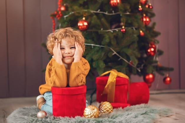 Garotinho perto de árvore de natal em um suéter marrom